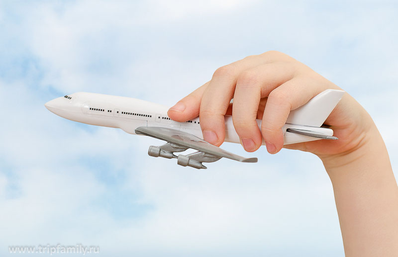 Child hand holding model airplane on sky background.